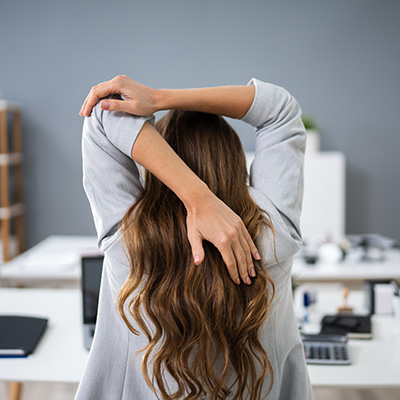 Business Woman Stretching at desk