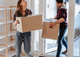 Couple Moving Boxes into Home