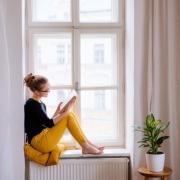 Girl Reading Book in Window
