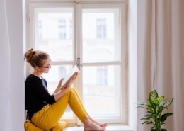 Girl Reading Book in Window